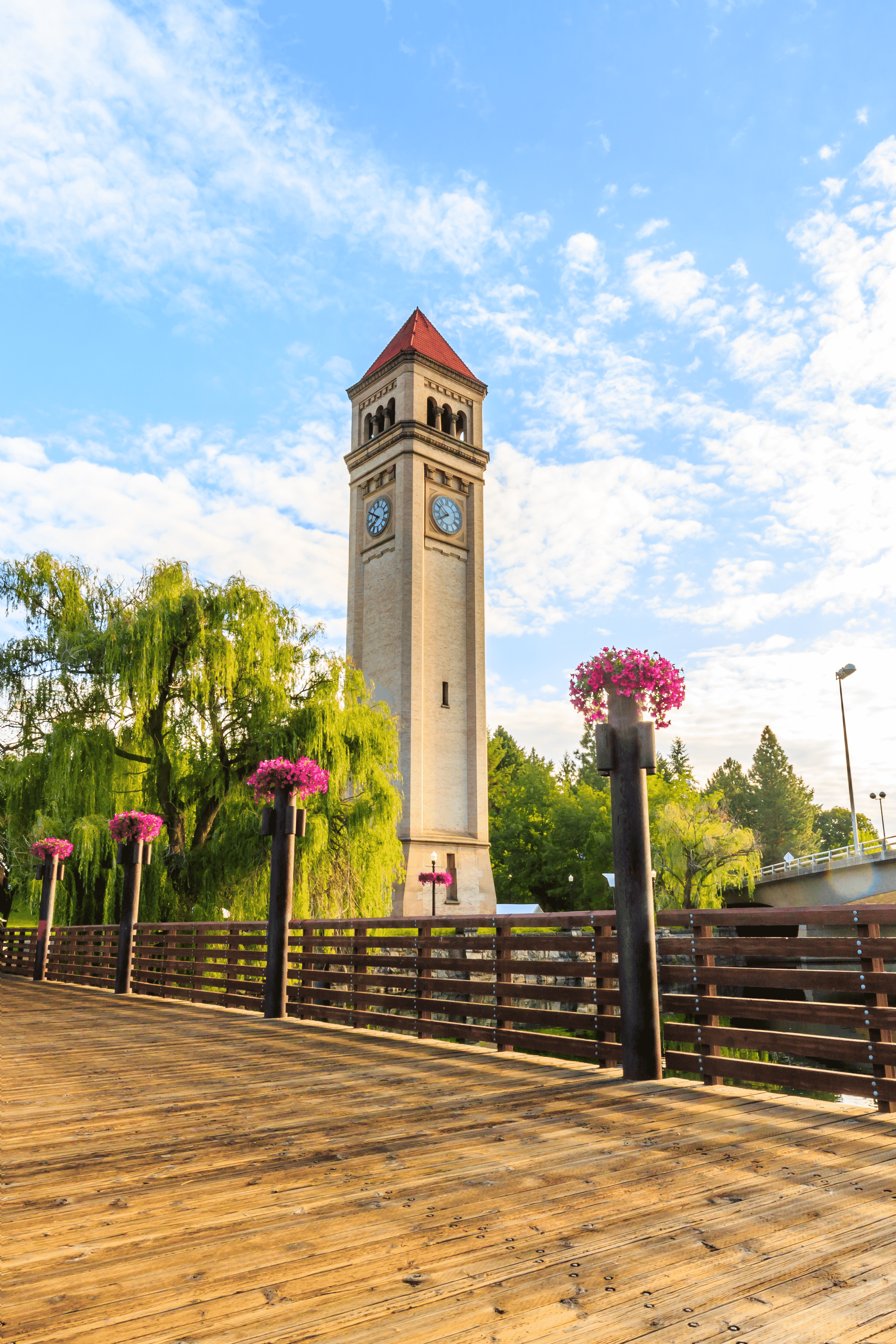 The Spokane clock tower surrounded by flowers and tree.